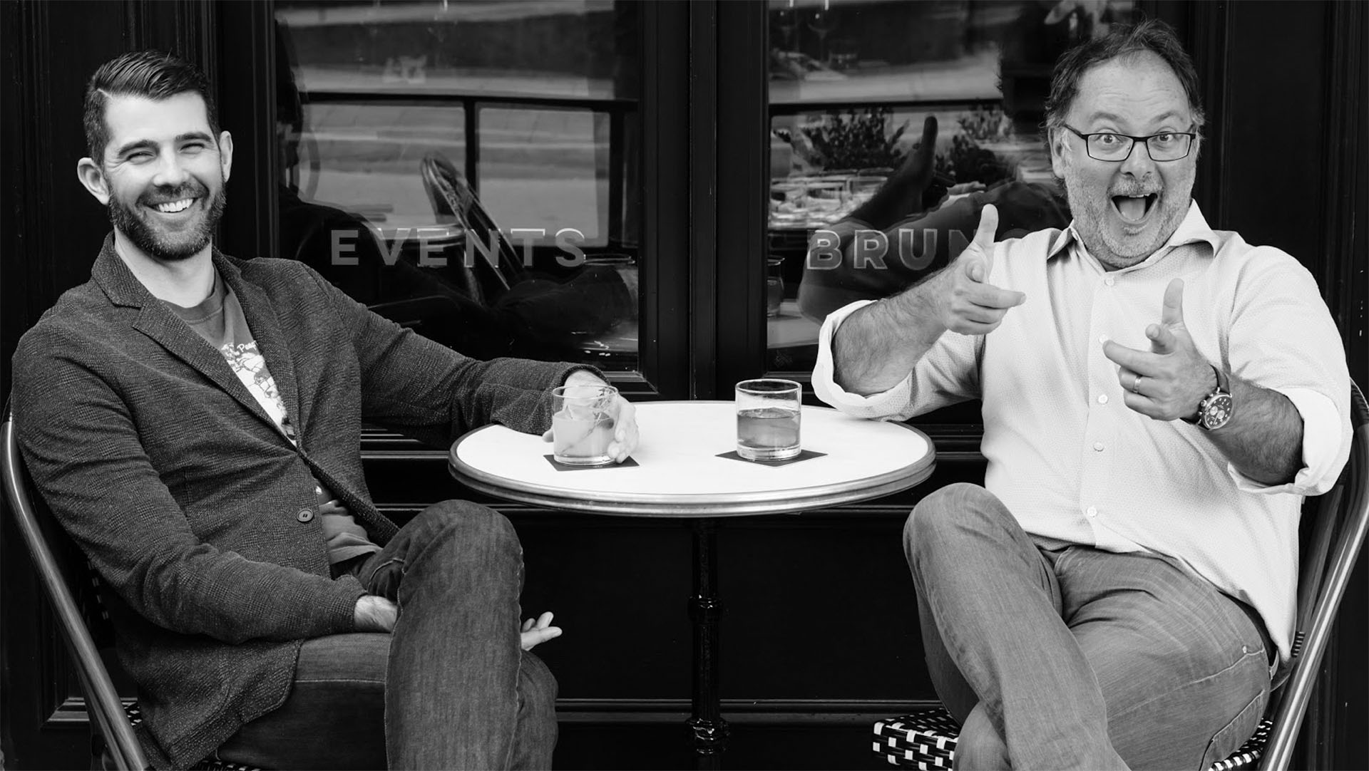 Jerrett Young and Jason Cassis sitting outside a cafe drinking coffee